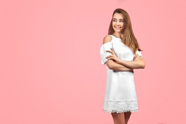 Hermosa chica con vestido blanco y posando sobre fondo rosa.
