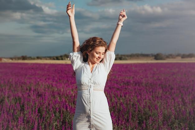 Hermosa chica en vestido blanco se está riendo en el campo de verano de lavanda