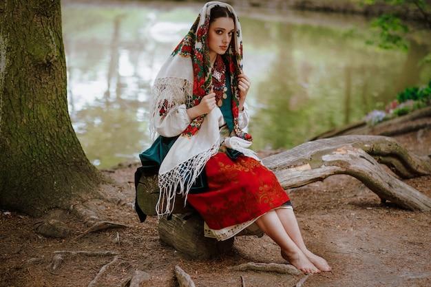 Hermosa chica en un vestido étnico tradicional sentado en un banco cerca del lago