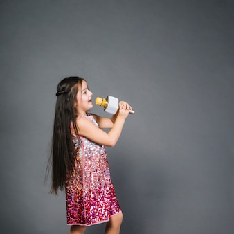 Hermosa chica en vestido de lentejuelas firmando canción con micrófono