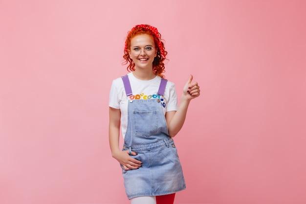 Hermosa chica en vestido de mezclilla y camiseta blanca con una sonrisa mirando a la cámara y mostrando los pulgares hacia arriba en la pared aislada