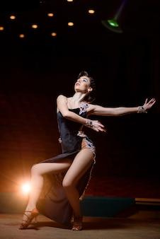 Hermosa chica en vestido negro bailando en el escenario.
