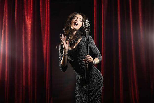 Hermosa chica en vestido negro cantando en el micrófono en la sala de conciertos