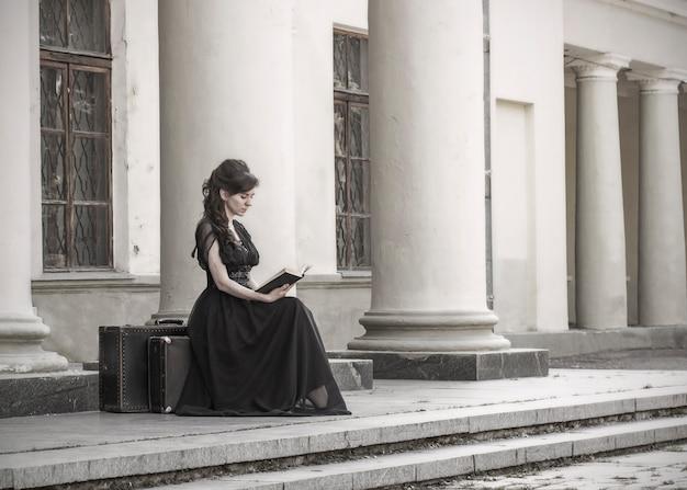 Hermosa chica en vestido de noche negro sentado leyendo un libro