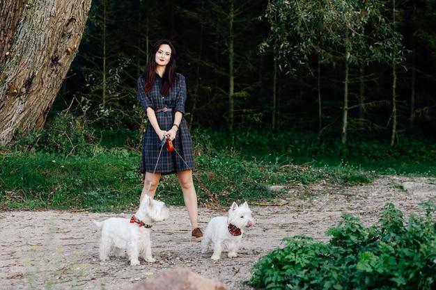 Hermosa chica en un vestido paseando a sus perros blancos en el parque
