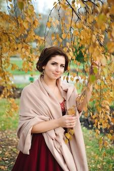 Hermosa chica con un vestido rojo en el bosque de otoño