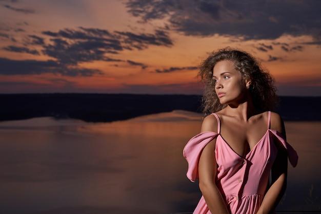 Hermosa chica en vestido sexy cerca del lago en la noche