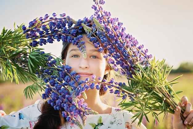 Hermosa chica en vestido sosteniendo un lupino al atardecer en el campo. el concepto de naturaleza y romance. infancia feliz