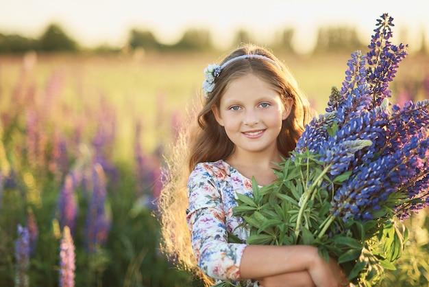 Hermosa chica en vestido sosteniendo un lupino al atardecer en el campo