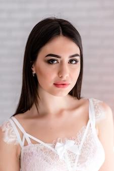 Hermosa chica en vestido de tocador de encaje blanco en la decoración de colores de fondo con ventana grande