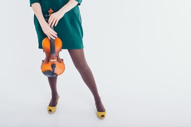 Hermosa chica en vestido verde con pequeña guitarra en las manos. publicidad de instrumentos musicales, moda, símbolos