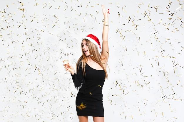 Hermosa chica vistiendo ropa de papá noel sostiene una copa de champán y tiene ventilador en sombrero rojo sobre el fondo blanco.
