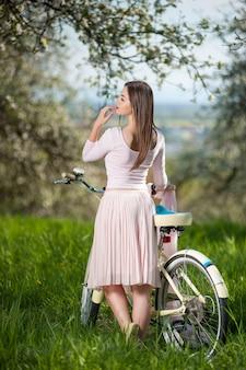 Hermosa ciclista femenina con bicicleta retro en el jardín de primavera