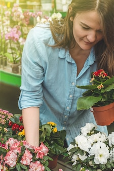 Hermosa clienta que huele coloridas macetas en flor en la tienda minorista. jardinería en invernadero. jardín botánico, cultivo de flores, concepto de industria hortícola