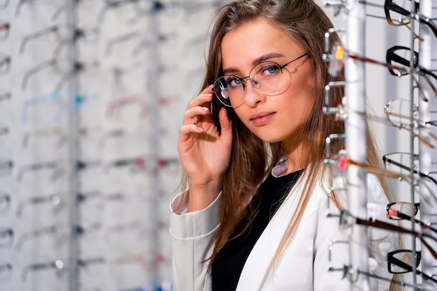 Hermosa clienta u óptico está de pie con primas de gafas en la tienda óptica