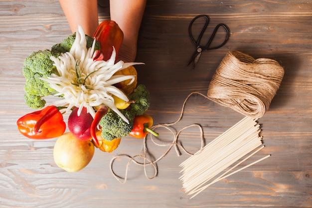 La hermosa comida: ramo comestible con flores y verduras de frutas talladas en estilo rústico