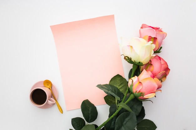 Hermosa composición con café, rosas rosadas y papel en blanco sobre blanco