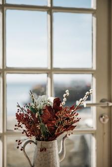 Hermosa composición de flores en una maceta junto a la ventana