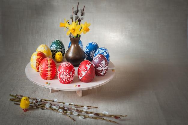 Hermosa composición con huevos pintados, ramas de sauce y ramo de flores de primavera.