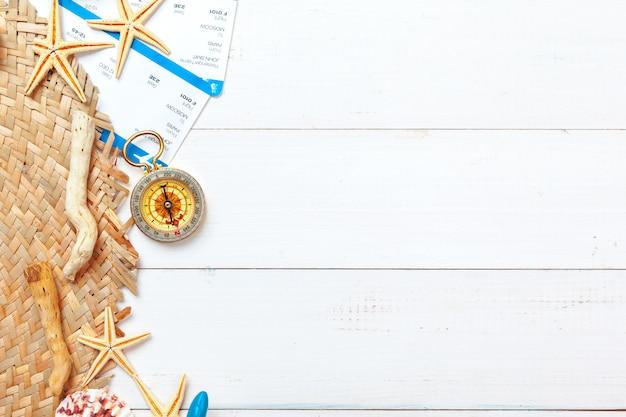 Hermosa composición de mar con conchas y brújula vintage sobre fondo blanco.