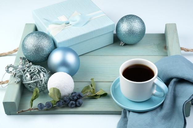 Hermosa composición navideña con una caja de regalo, una taza de bolas de café y una rama con bayas en una bandeja azul suave