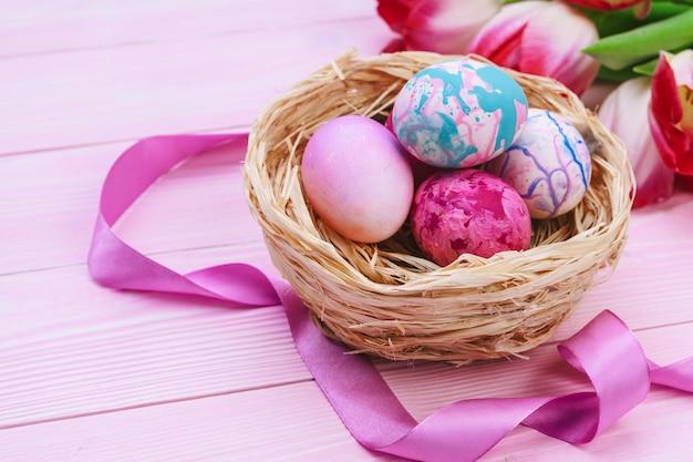 Hermosa composición de pascua con huevos decorados y flores en la mesa de madera en colores pastel