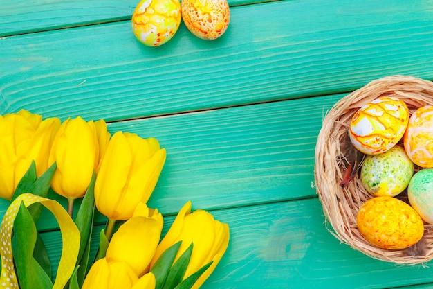 Hermosa composición de pascua con huevos decorados y flores sobre fondo de madera en colores pastel