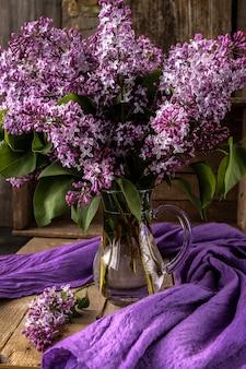 Hermosa composición con ramo de lilas en mesa vieja