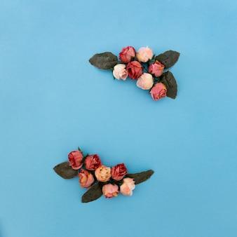 Hermosa composición de rosas y plantas sobre fondo azul