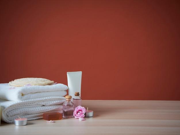 Hermosa composición de spa con aceite aromático, rosas en mesa de madera