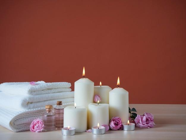 Hermosa composición de spa con velas aromáticas encendidas y aceite aromático, rosas rosadas en la mesa de madera