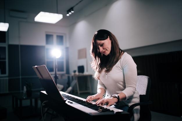 Hermosa compositora femenina tocando el piano.