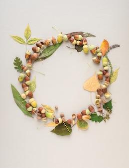 Hermosa corona hecha de bellotas y hojas de diferentes tamaños sobre un fondo morado claro