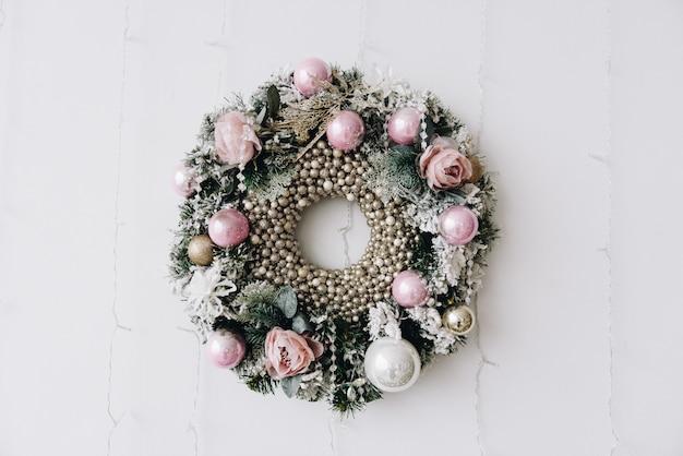 Hermosa corona de navidad en rosa y plata colgada en una pared.