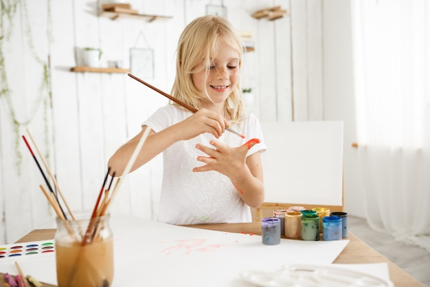 Hermosa, creativa y ocupada niña rubia en camiseta blanca dibujando en su palma con un pincel.