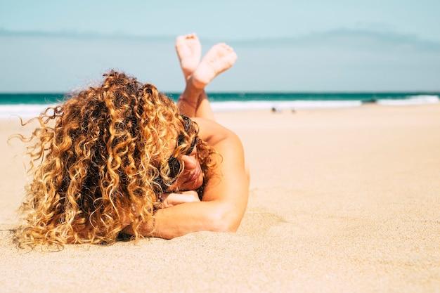Hermosa dama bronceada atractiva de mediana edad con cabello rubio rizado se acuesta en la playa para un baño de sol de verano durante las vacaciones