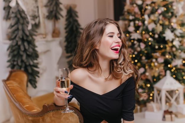 Hermosa dama de cabello oscuro en traje negro posando en el día de año nuevo con copa de champán. foto interior de guapa modelo femenina europea celebrando la navidad en casa y riendo.