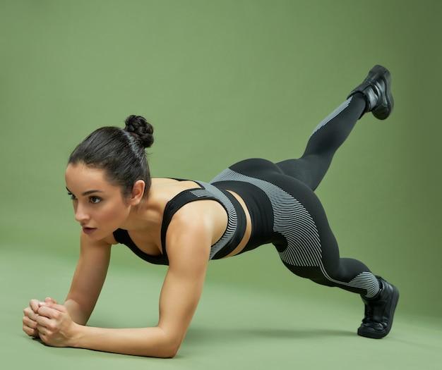 Hermosa dama en forma sosteniendo la posición de plancha y levantando la pierna mientras hace ejercicio de fuerza. aislado sobre fondo verde