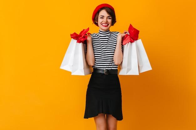 Hermosa dama francesa sosteniendo bolsas de tienda y sonriendo