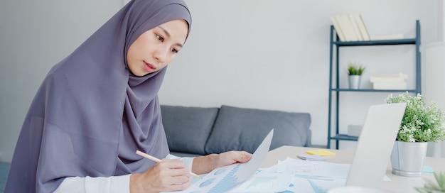 Hermosa dama musulmana de asia en ropa casual con pañuelo en la cabeza usando la computadora portátil en la sala de estar en casa.