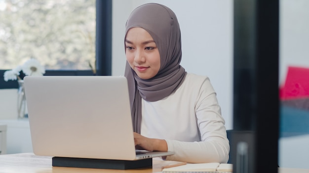 Hermosa dama musulmana asiática ropa casual trabajando con ordenador portátil en la nueva oficina normal moderna.
