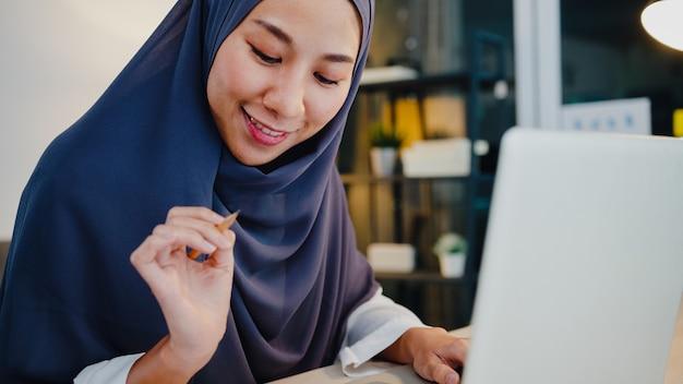 Hermosa dama musulmana en ropa casual con pañuelo en la cabeza con laptop en la sala de estar en la casa de noche.