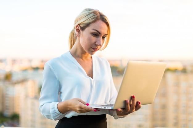 Hermosa dama de negocios inteligente de pie en el techo con la computadora portátil en las manos