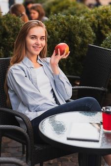 Hermosa dama rubia sosteniendo una manzana
