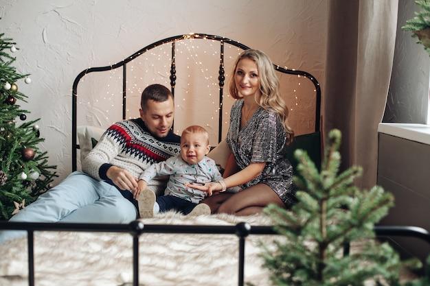 Hermosa dama rubia con su amado esposo y un niño lindo sentado en una cama cerca del árbol de navidad