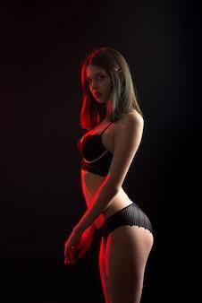 Hermosa dama tímida en bragas de sujetador de tocador de bikini de encaje. licitación forma delgada aislado negro