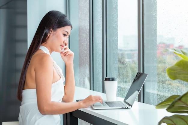 Hermosa dama tocando portátil y compras en línea en la sala de estar.