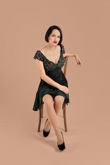 Hermosa dama en vestido corto sentado en una silla en estudio con fondo beige