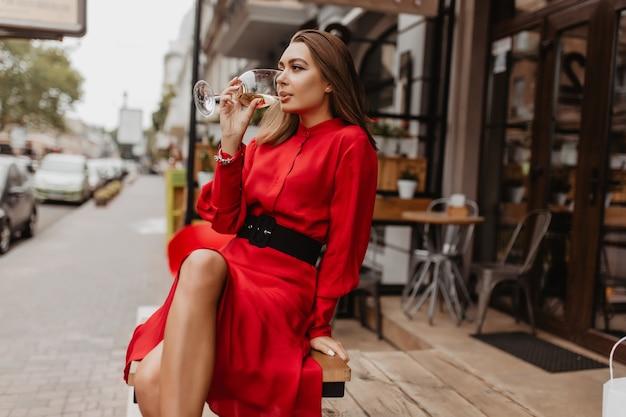 Hermosa dama con vestido de diseñador caro bebe delicioso vino espumoso de cristal. foto de cuerpo entero de blogger sentado en la cafetería