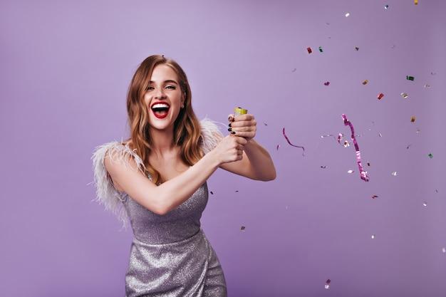 Hermosa dama en vestido plateado lanzando confeti en la pared púrpura